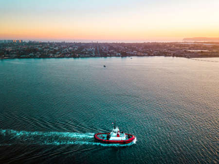 Aerial photo of a small tugboat sailing in San Diego bay area at sunset