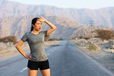 Tired runner taking a rest on a desert road Stock Photo - 102926081