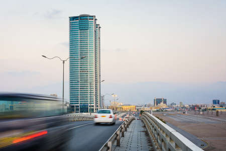 Ras Al Khaimah city scene with tower view and car passing the bridge