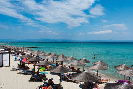 Chaniotis, Greece - June 23, 2018: Chaniotis city beach and clear sea of Chalkidiki with many tourists, Greece seaside destination