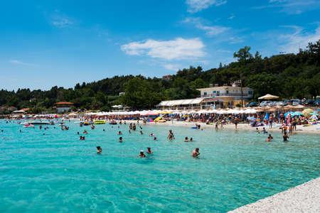 Chaniotis, Greece - June 23, 2018: Popullar Chaniotis city beach in Kassandra, Chalkidiki with many tourists enjoying the sunny day Editorial