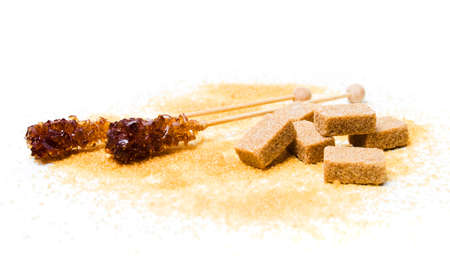 Brown sugar sticks, crystals and cubes on white