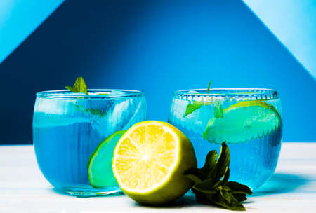 Blue cocktails decorated with lemon on matching background