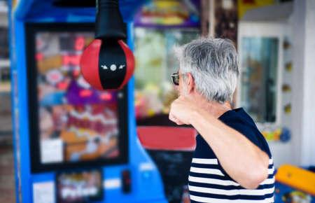 Senior man punching the boxer arcade at carnival