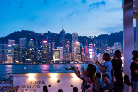 Hong Kong - August 7, 2018: Tourists enjoying the view of Hong Kong downtown cityscape view from the newly built Avenue of Stars