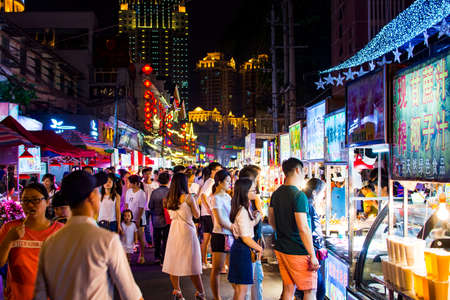 NANNING, CHINA - JUNE 9, 2017: Nanning Zhongshan Snack Street with many people bying food and walking around. This food street is the biggest night food market  in the capital city of Guangxi province in China