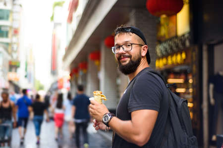 Foreigner eating Chinese street food on the street