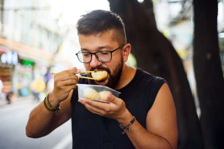 Foreigner eating baozi on the street in China