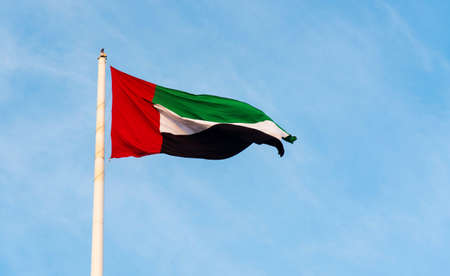 United Arab Emirates flag winding in the wind against blue sky Stock Photo - 114489180