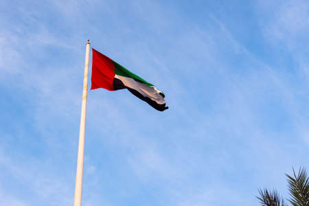United Arab Emirates flag winding in the wind against blue sky Stock Photo - 114490857