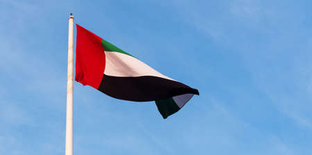 United Arab Emirates flag winding in the wind against blue sky Stock Photo - 115048202