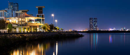 Ras Al Khaimah, United Arab Emirates - October 30, 2018: Panoramic view of Ras Al Khaimah creek night view with calm water at evening, the heart of northern emirate of the UAE
