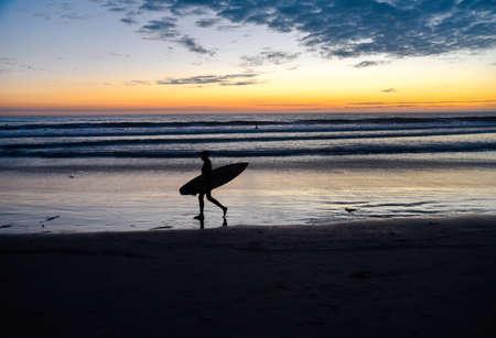Silhouette di un surfista che trasporta una tavola da surf