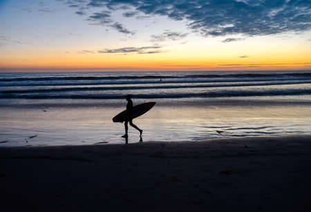 Surfer silhouette carrying a surfboard Archivio Fotografico