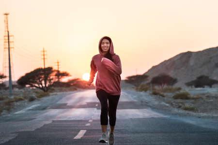 Girl running in sunset wearing a pink hoody 写真素材