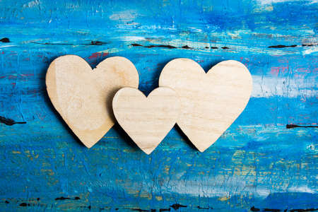 Wooden hearts on a blue table top view