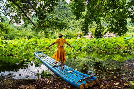 Girl standing on bamboo raft in lotus flower lake