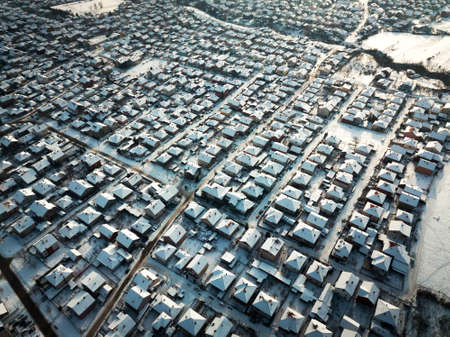 Aerial of a lot of rooftops covered with snow Imagens
