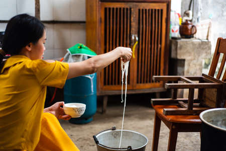 Woman taking out homemade noodles by hand at home