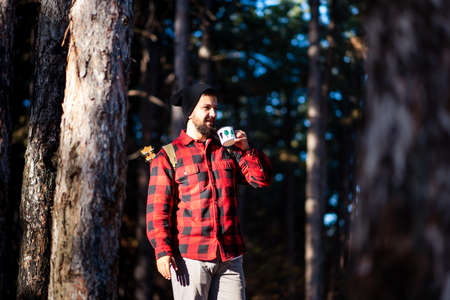 Man having a cup of coffee in the woods