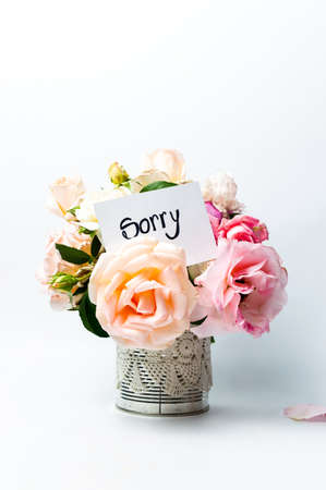 Rose flowers bouquet in a vase with a sorry note