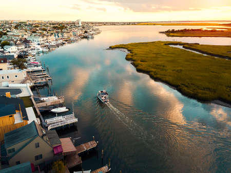 Aerial photo of a boat sailing in still water of the bay at sunset