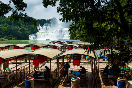 Chongzhuo, China - July 25, 2018: Tourist boats by the Detian Ban gioc waterfalls on China and Vietnam border