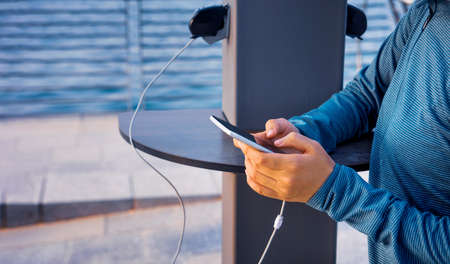 Female using phone and charging on a public charger