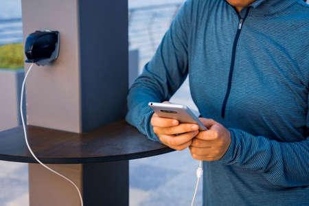 Frau, die Telefon benutzt und an einem öffentlichen Ladegerät auflädt