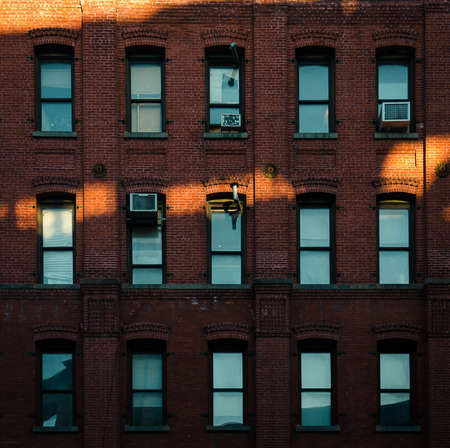 Red brick facade with blue windows and sun rays in New York Stock Photo