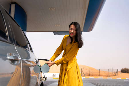 Woman adding gasoline on the fuel station alone