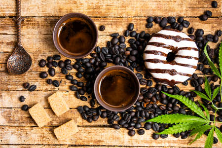 Coffee beans with marijuana plant tabletop view