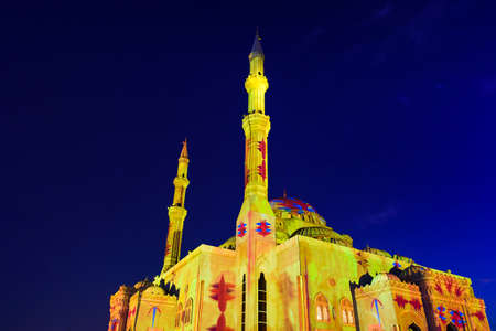 Illuminated mosque in emirate of Sharjah during light festival Stock Photo
