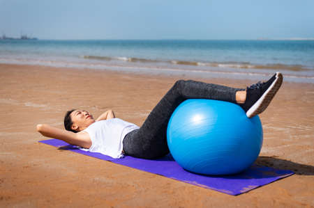 Woman exercising with pilates yoga ball on the beach Banco de Imagens