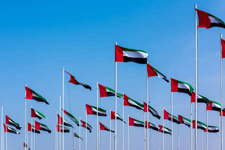 Many United Arab Emirates flags winding in the wind against blue sky Фото со стока