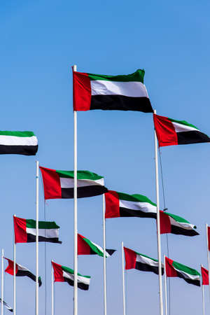 Many United Arab Emirates flags winding in the wind against blue sky Stock Photo