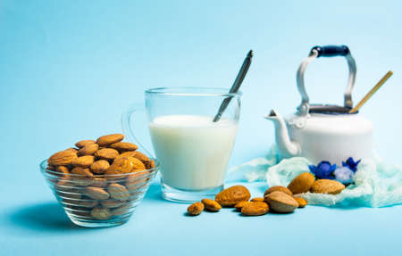 Almond milk and nuts in a glass against blue background