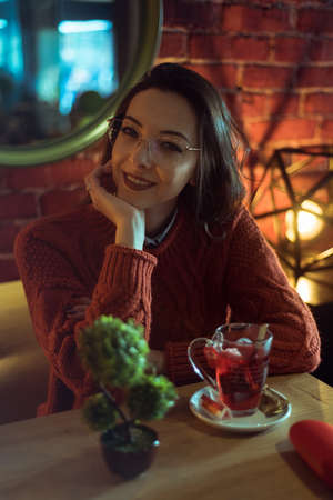 smiling brunette with glasses in a coffee shop 版權商用圖片