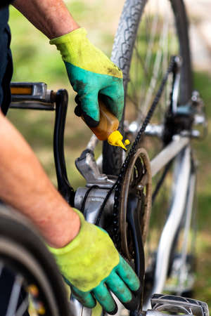 Man lubricating bicycle chain and maintaining for the new season 版權商用圖片