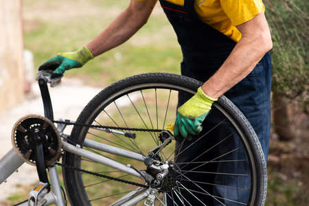 Man lubricating bicycle chain and maintaining for the new season 스톡 콘텐츠 - 118928255