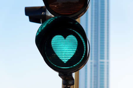 Heart shaped traffic light on the street close up