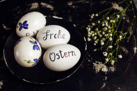Happy easter written in German on white eggs with flowers
