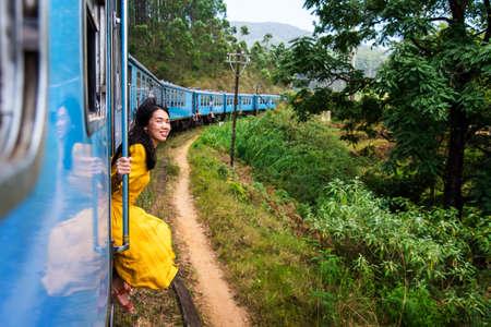 Woman sitting by the blue train door Sri Lanka