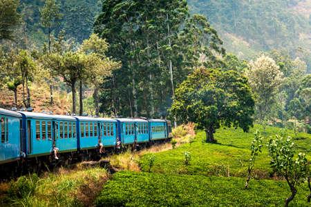 Scenic blue train slowly going through Sri Lanka highlands