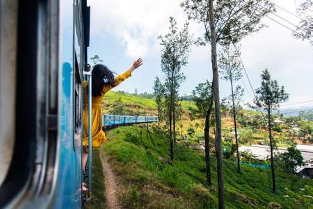 Woman enjoying the train ride through Sri Lanka tea plantations