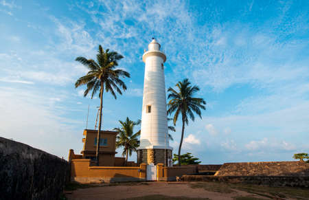 Galle Dutch Fort lighthouse and coconut trees in Sri Lanka