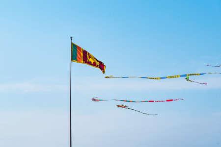 Flag of Sri Lanka waving against blue sky