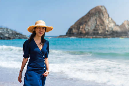 Fashionable Asian girl walking on the beach on summer vacation