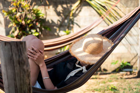 Woman relaxing on a hammock on the beach Stock Photo