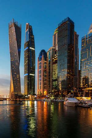 Dubai, Verenigde Arabische Emiraten - 14 februari 2019: Dubai jachthaven moderne scène van wolkenkrabbers en luxe jachten op het blauwe uur Redactioneel